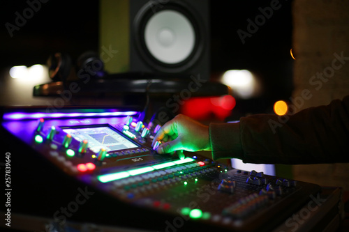 Sound engineer in action over a concert night of live music  - 257839640