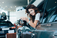Selective Focus Of Happy Curly Woman Holding Keys While Looking Out Of Window In Automobile