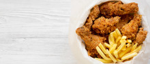 Fast Food: Fried Chicken Drumsticks, Spicy Wings, French Fries And Chicken Strips In Paper Box Over White Wooden Surface, Top View. Copy Space.