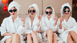 Urban leisure and lifestyle. Arrogant women with champagne. Sunglasses, bathrobes and towel turbans on. Bare legs.