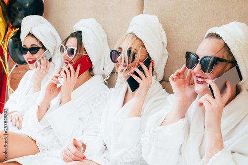 Cheerful spa girls talking on smartphones Canvas Print