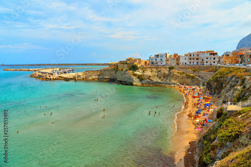 Foto auf AluDibond Olivgrun beautiful landscape in small coastal town Terrasini with beach calarossa with Faraglioni di Praiola with turquoise blue water and cloudy blue sky in background, Sicily Italy Palermo