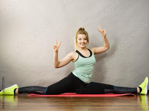 Fotobehang School de yoga Woman in sportswear stretching legs doing twine