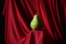 Green Pear On Red Background