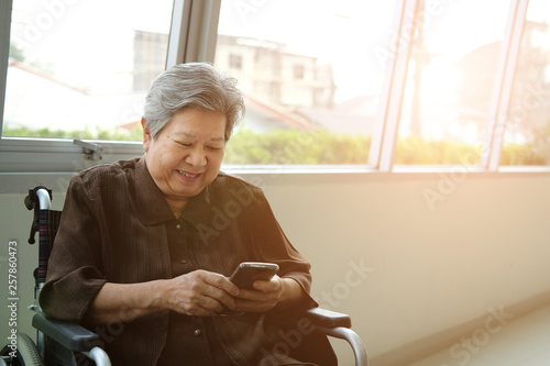 Photo  elder woman in wheelchair holding mobile phone