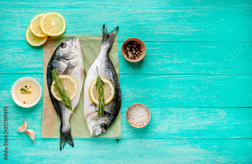 Fotografie, Obraz  Two fresh raw Dorado fish with spices and olive oil on a wooden table