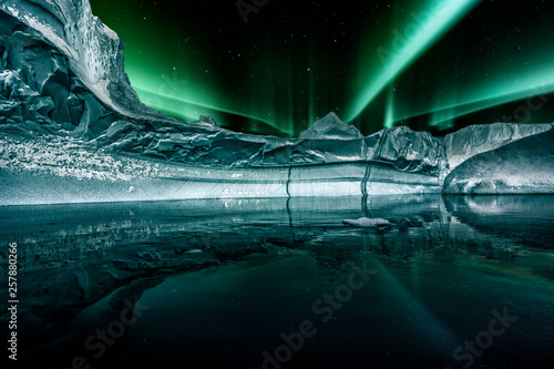 Poster Aurore polaire iceberg floating in greenland fjord at night with green northern lights
