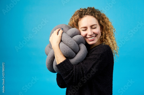 Fotomural Young attractive smiling cheerful curly ginger girl hugs a soft toy with pleasure