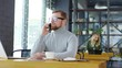 Cheerful redhead businessman in eyeglasses and casual wear smiling and speaking on mobile phone while sitting at table in cafe on coffee break and looking through the window