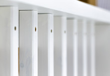 White Painted Wooden Deck Railing. Selective Focus On Balusters With Fastener Screws