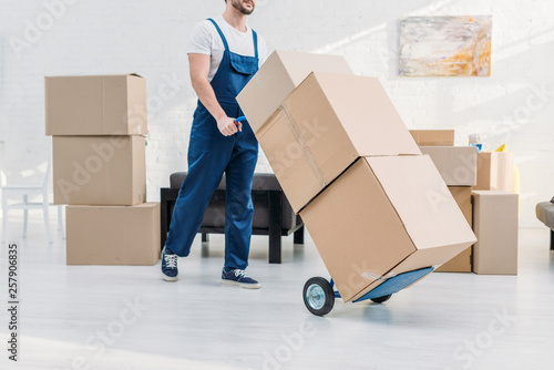 Fotografiet  cropped view of mover in uniform transporting cardboard boxes on hand truck in a