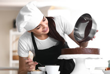 Young Female Confectioner Cooking Tasty Cake In Kitchen