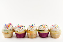 Five Mini Cupcakes In A Row Isolated On White Background.  Confetti Cake With White Icing With Rainbow Sprinkles. Copy Space Above.