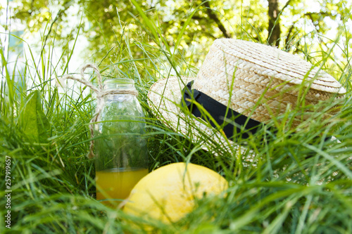 Poster Jardin A straw hat is lying on the grass outdoors with a yellow citrus fruit and a bottle of lemonade. Picnic on nature in the park on a background of trees with bright sunshine