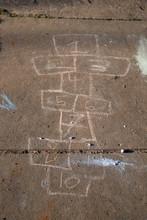 Hopscotch Board Drawn With Sidewalk Chalk On Gray Pavement Background
