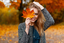 Happy Cute Young Attractive Woman With A Smile In A Fashionable Coat Is Standing In The Park And Covering Her Face With Yellow Autumn Maple Leaves. Funny Positive Girl. Emotion Of Joy.