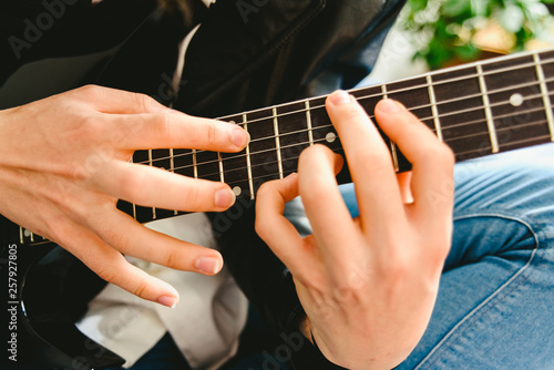 Photo Detail of the fingers of a guitarist placed on the fret of the mast of the guitar playing a chord doing Tapping
