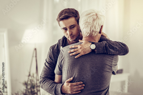 Twenty-years-old dark-haired kind male calmingly cuddling sick sorrowful aging g Fototapeta