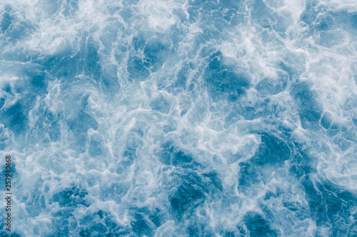 Foto auf Gartenposter Wasser Pale blue sea surface with waves, splash, white foam and bubbles at high tide and surf, abstract background