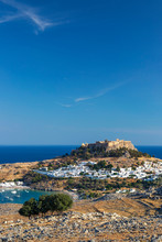 View Of Lindos Acropolis With City Against Blue Sky