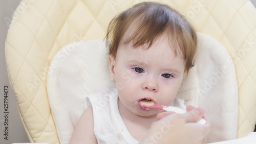 Valokuvatapetti Mother feeds baby from spoon. Learn to eat.