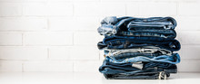 A Stack Of Old Jeans On A Light Background