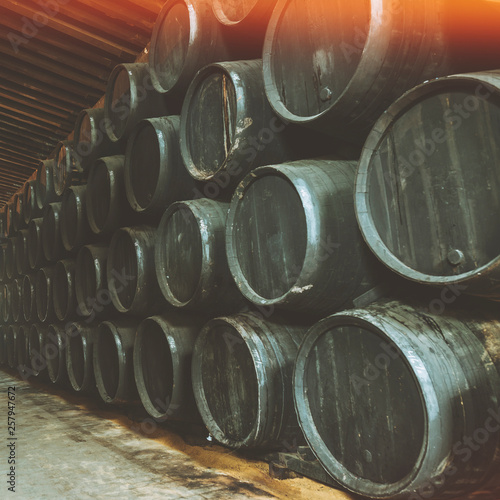 Fototapeta Barrels for whiskey or wine stacked in the cellar