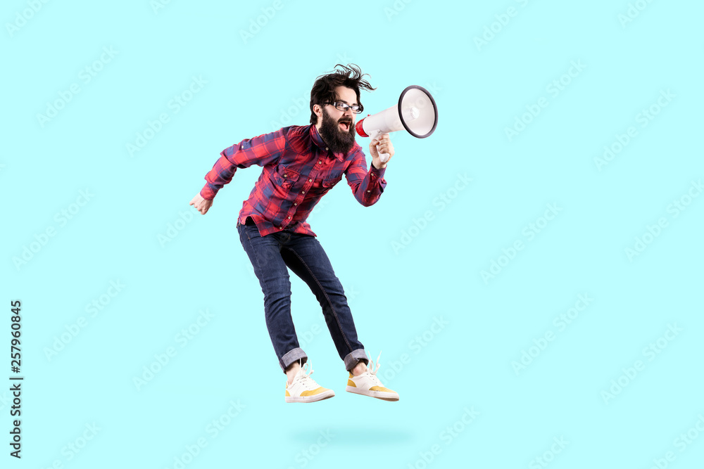 Fototapeta Bearded hipster man in glasses, jumping and shouting in megaphone, photo on blue background