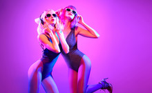 Fashion. Two DJ Girl With Dyed Hair In Colorful Neon Light Enjoy Music, Friends. Party Disco 80s 90s Vibes. Model Woman In Fashionable Bodysuit Dance, Makeup. Creative Art, Dancing Concept