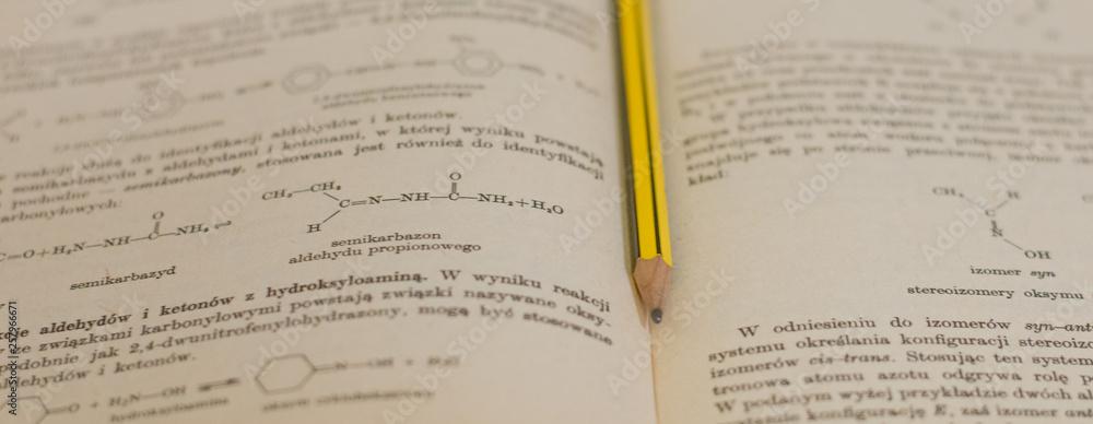 Fototapeta żółty ołówek na tle książki do chemii