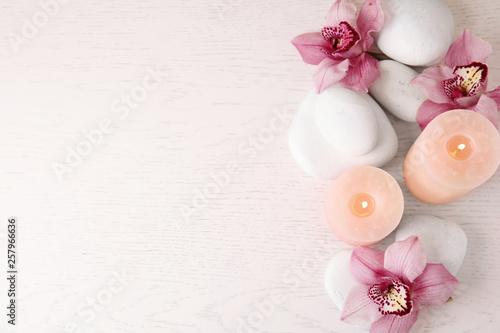 Flat lay composition with zen stones, candles and flowers on wooden background. Space for text
