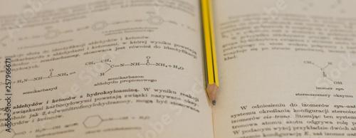 Obraz żółty ołówek na tle książki do chemii - fototapety do salonu