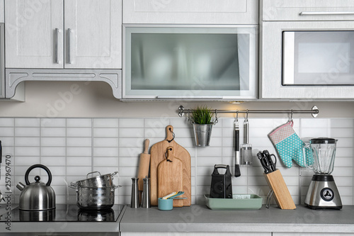 Photo Kitchen interior with clean cookware, appliances and dish cabinet