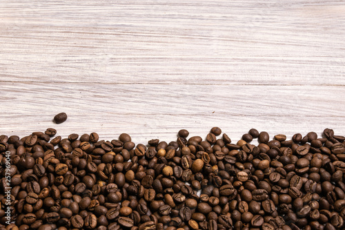 Fototapety, obrazy: Roasted coffee beans in bulk on a light wooden background. dark cofee roasted grain flavor aroma cafe, natural coffe shop background, top view from above, copy space