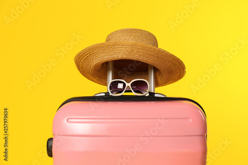 Valokuvatapetti Stylish suitcase with hat and sunglasses on color background