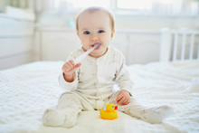 Cute Little Girl With Toothbrush In Pyjamas On Bed