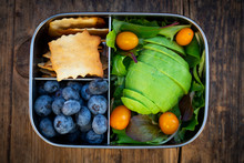 Lunch Box Of Leaf Salad, Avocado, Blueberries, Tomatoes And Crackers