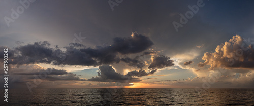 Abstract seascape panoramic background - Orange color in the sky, sunset late afternoon. Calm seas/ocean in the bottom of the frame. Minimalistic simple background image, blue and yellow colors.