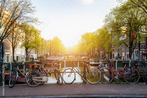 Bike over canal Amsterdam city in Netherlands with view on river Amstel during sunset. #257990206