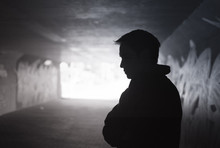 Depressed Sad Young Man Standing In A Dark City Tunnel