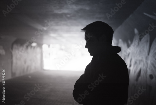 Obraz Depressed sad young man standing in a dark city tunnel  - fototapety do salonu
