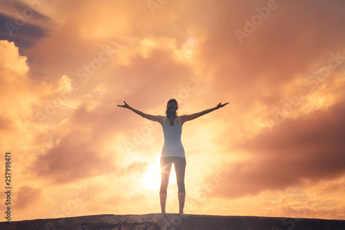 young woman with arms up to the sky feeling free and happy Canvas Print