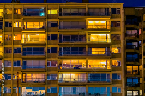 lighted city apartments by night, Belgian city architecture with windows and bal Fototapet