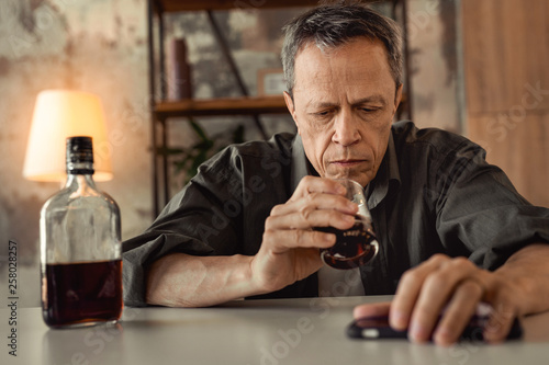 Fotografija Disappointed battered old man having life problems and using alcohol