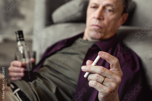 Fotografia  Attentive old man playing with cigarette while carrying bottle of whisky
