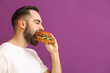 Man eating tasty burger on color background