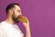 Man eating tasty burger on color background