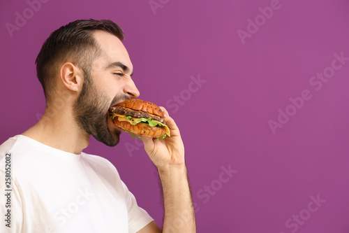 Man eating tasty burger on color background Canvas Print