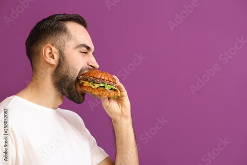 Fototapeta Man eating tasty burger on color background obraz