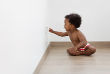 Baby Sitting On The Floor Touching Electrical Plug